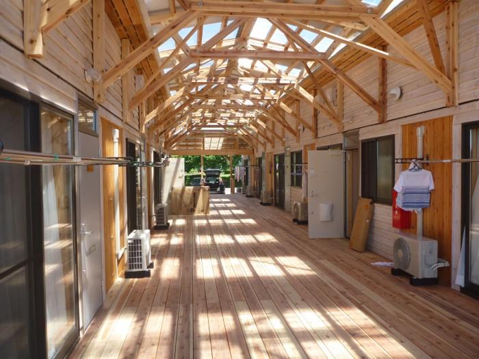 ケアゾーンのデッキを挟んで向き合う住戸. 上部に透過性の屋根が架かり半屋外空間となる(遠野市)